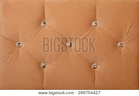 Close up background of pastel beige color soft velvet bed headboard with rhinestone crystals, front view poster