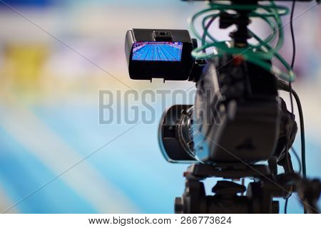 Modern camera during reporting from swimming basin, shallow dof.