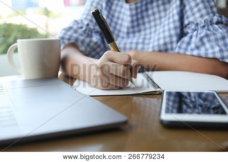 Business Woman Holding Pen Writing On White Empty Notebook On Wooden Table. Close Up Hand Using Pen