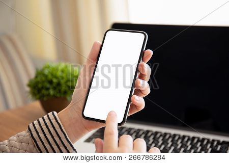 Female Hand Holding Touch Phone With Isolated Screen Above The Table With Laptop In The Office