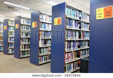 A view of rows of bookshelves and a study area inside a library