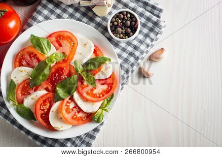 Photo Of Caprese Salad With Tomatoes, Basil, Mozzarella, Olives And Olive Oil On Wooden Background.