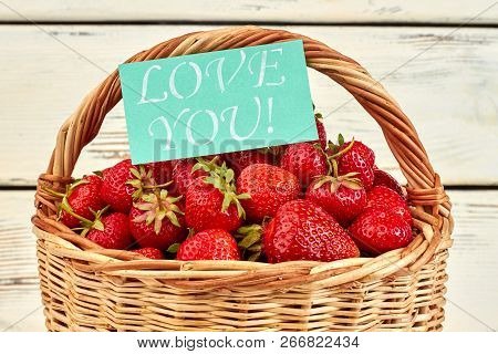 Basket of freshly picked strawberries. Ripe juicy strawberries and message love you. Fruity summer love. poster