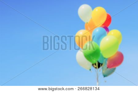 Defocused Background Of Colorful Helium Balloons Isolated On Background. Intentionally Blurred Post