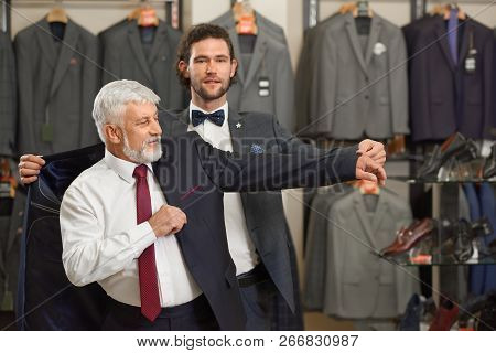 Young Brunette Son Helping His Grey Haired Father Choosing Costume. Atractive Guy And Older Grey Man