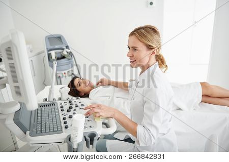Young Doctor Using Ultrasound Scanner And Examining Thyroid Of Young Lady