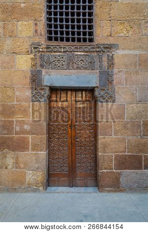 Wooden Ornate Door With Geometrical Engraved Patterns On External Old Decorated Bricks Stone Wall Le