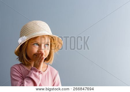 Adorable Little Four Year Old Girl Wearing An Elegant Straw Hat Whispering A Secret With Her Hand To