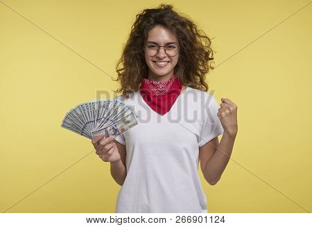 Pretty Young Female Holds Cash In The Hand And Shows Yes Sign By The Hand, Isolated Over Yellow Back