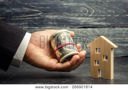Wooden House And Money In Hand. A Loan Secured By Real Estate. Home Renovation And Repair. Warm Loan