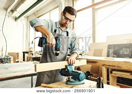 Concentrated young carpenter drilling hole in piece of timber using portable electric drill in his w