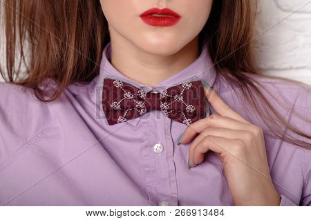 Close Up Of Young Woman Adjusting Her Bow Tie In Red Shirt. Elegant Girl Model Poses In Blouse And B