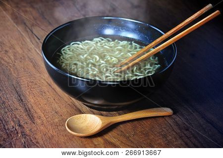 Wooden Chopsticks And Spoon Of Instant Noodles With Smoke.steam From Hot Soup Bowl Selective Focus.i