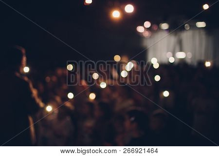 Blurred is not a sharp abstract concert fun background. Large crowd of spectators, fans of rock concert during music show during night. Spectators in sand of beach Selective BLUR focus. poster