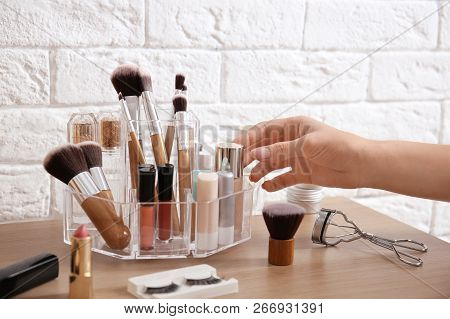 Woman Taking Liquid Foundation From Organizer For Makeup Cosmetic Products On Dressing Table