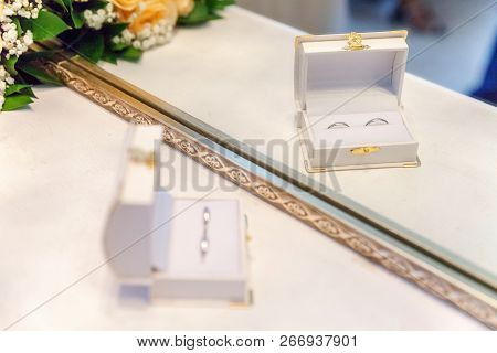 Two Beautiful Wedding Rings On White Jewelry Box On Light Background. Declaration Of Love Wedding Ca