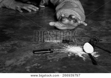 A Man Is A Drug Addict With A Syringe Using Drugs Lying On The Floor. The Concept Of Anti Drugs. Mal