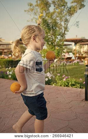 Boy Playing With Oranges Or Citrus Fruit On Sunny Summer Day In Park. Cute Smiling Child, Small Litt