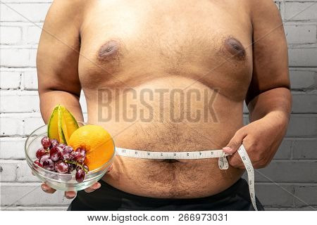 Fat Man Diet With Fruit Using Measuring Tape To Measuring His Stomach At Home. Fat Man Diet
