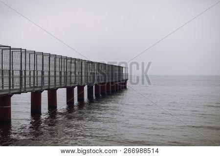 Attractive View Of The Pier. Perspective Of The Metal Structure Of A Rusty Pier.