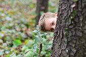 The thrill is in the discovery. Small boy play hide and seek. Small boy enjoy playing outdoor. Its a game of hide-and-seek. Its fantastic game. poster