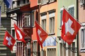 Old street in Zurich decorated with flags for the Swiss National Day, 1st of August poster