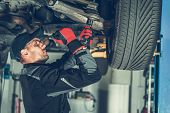 Caucasian Car Mechanic Adjusting Tension in Vehicle Suspension Element. Professional Automotive Service. poster