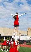 High school cheerleaders practice a routine beore homecoming with three girls balancing their teammate up over their heads in the air. poster