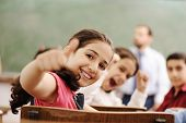 Happy children smiling and laughing in the classroom, showing thumb up, successful pupils and teacher poster