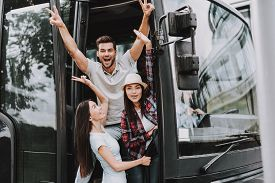 Young Smiling People Traveling On Tourist Bus. Group Of Happy Friends Standing Together In Doors Of