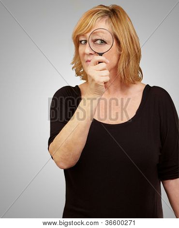 Woman using a magnifying glass isolated on gray background poster