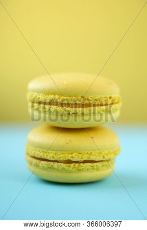 Yellow traditional french macaroons on yellow and blue background