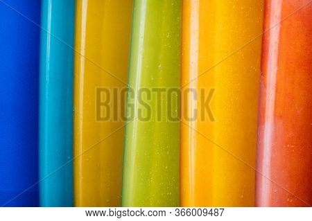 Close Up Set Of Different Color Surf Boards In A Stack On Sandy Beach For Rent. Multicolored Surfboa