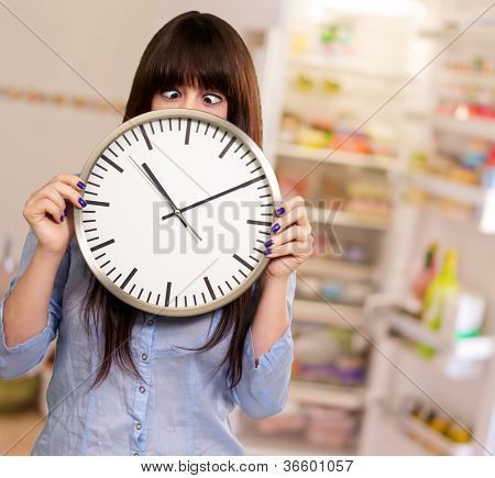 Woman Holding Clock With Squinted Eyes, Indoor
