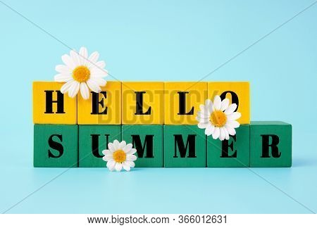 Hello Summer Text Written On Two Rows Of Yellow And Green Wooden Blocks Decorated With Chamomile Flo
