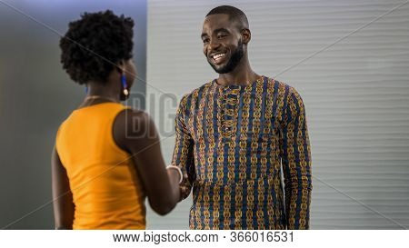 Two Young African Businesspeople Smiling And Shaking Hands Together While Standing In A Modern Offic