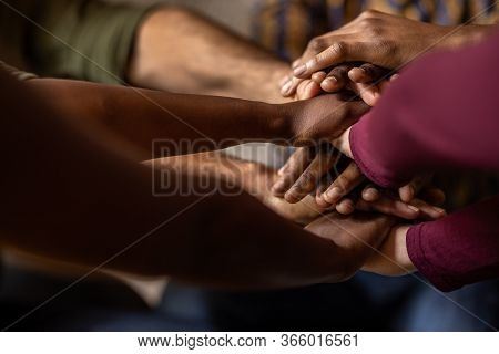 Closeup Of A Diverse Team Of Businesspeople Sitting In A Huddle With Their Hands Together In An Offi