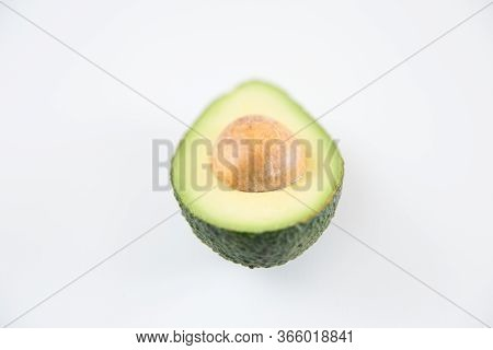 Single Cut Half Of Avocado With Core. Closeup Shot. Isolated Object On White Background. Fresh Food