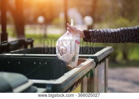 Hand With A Bag Of Plastic Garbage Over Containers For Separation And Sorting In Russia With The Wor