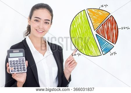 Female Banker Showing Profit On Calculator And Drawing Pie Chart. Portrait Of Happy Young Caucasian