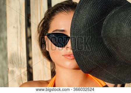 Young Woman Covering Face With Summer Hat. Sensual Girl Sunbathing By The Pool. Stylish Girl In Tren