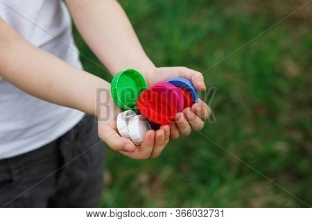 A Little Girl Holds Plastic Bottle Caps In Her Hands. Volunteer Charity Event \