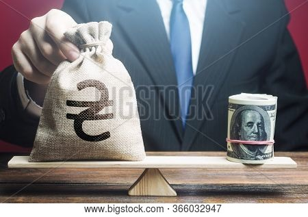 Man Puts A Ukrainian Hryvnia Money Bag On Scales Opposite To Dollar Bundle. Monetary Policy. Exchang