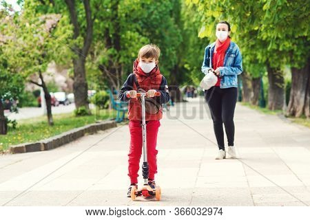 Riding Boy On Scooter In Park. Boy Wears Medical Face Mask. Mother And Son On A Walk During Coornavi