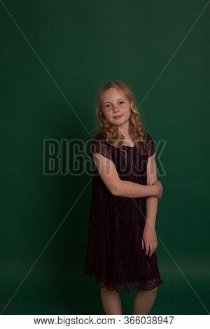 Portrait Of A Beautiful Little Blonde Girl In A Dark Dress