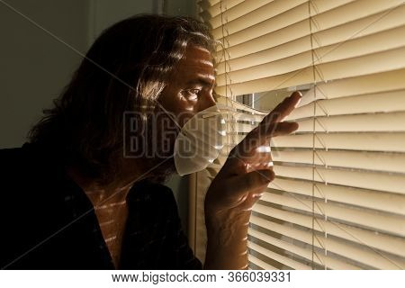 Coronavirus, Male Wearing Medical Mask In Self Isolation Looking Out Of Window Blinds Of Home. Worri