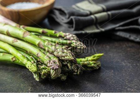 Fresh green asparagus. Healthy seasonal vegetable on black table.