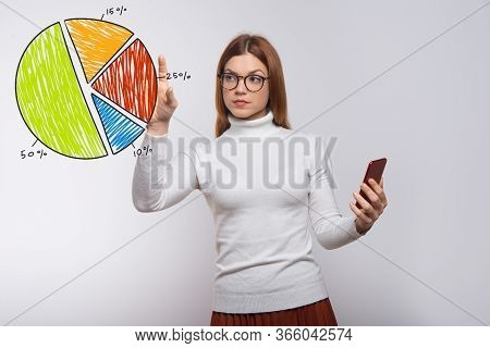 Concentrated Young Woman Using Smartphone And Drawing Pie Chart. Focused Lady In Eyeglasses Touching