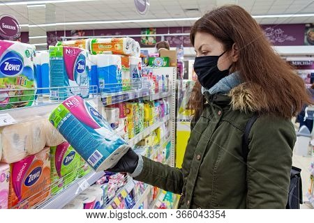 Minsk, Belarus - April 27, 2020: A Buyer In A Protective Mask Chooses Toilet Paper In A Supermarket