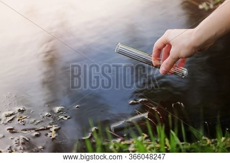 Scientist And Biologist Hydro-biologist Takes Water Samples For Analysis Outdoors. Hand Is Collects